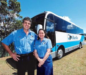 Man and Woman standing in front of bus